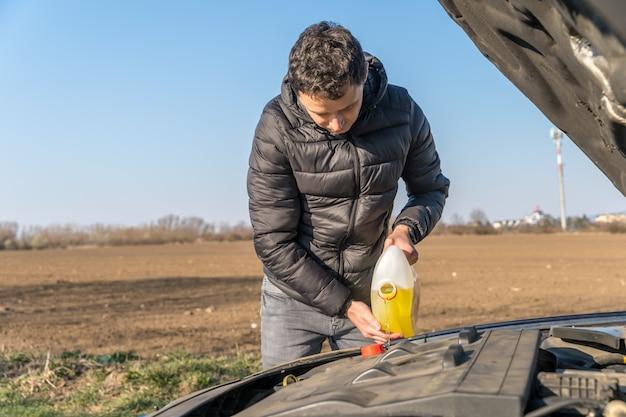 Mann gießt in das auto gelbe flüssigkeit für den scheibenwischer