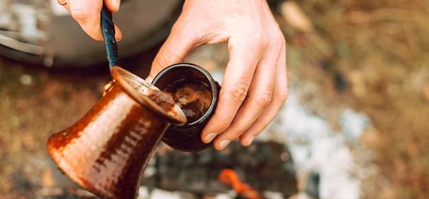 Mann gießt kaffee aus einer türkischen kaffeekanne in eine kleine tasse am morgen auf dem feld