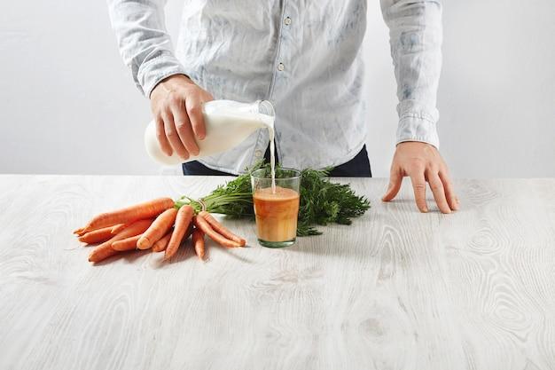 Mann gießt milch von flasche zu glas mit frisch gepresstem natürlichem karottensaft