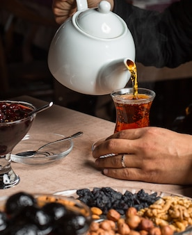 Mann gießt schwarzen tee aus der teekanne, serviert mit getrockneten früchten, marmelade