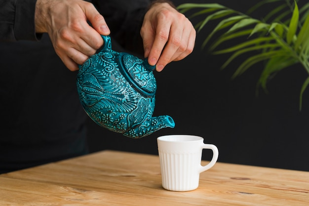 Mann gießt tee in tasse