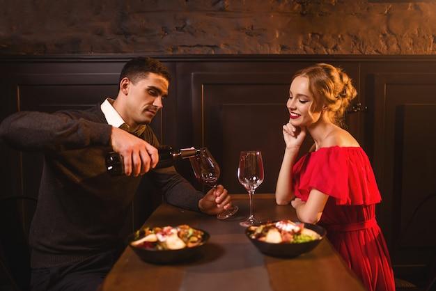 Mann gießt wein in ein glas, junges liebespaar im restaurant, romantisches date. elegante frau im roten kleid und ihr mann, jubiläumsfeier