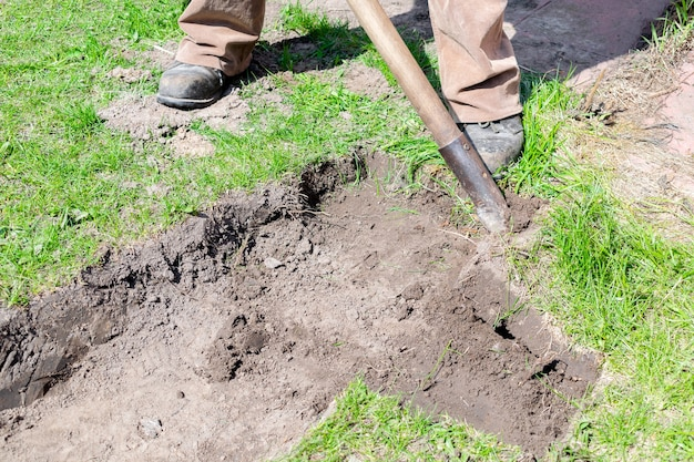 Mann gräbt boden rasen rasen im stadtpark garten oder hinterhof garten landschaftsbau service