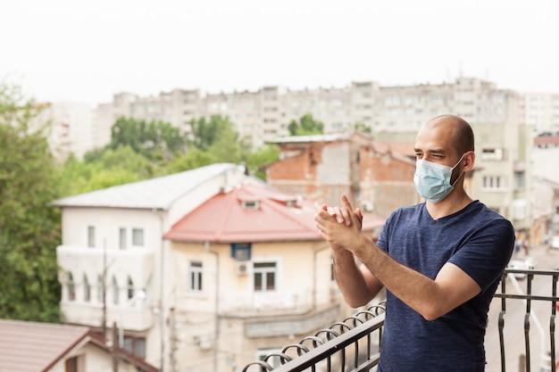 Mann gratuliert medizinischem personal, das von seinem wohnungsbalkon klatscht.