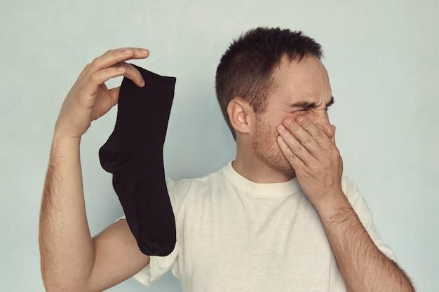 Mann greift nase mit fingern, die eine stinkende socke in der hand auf blauem hintergrund halten