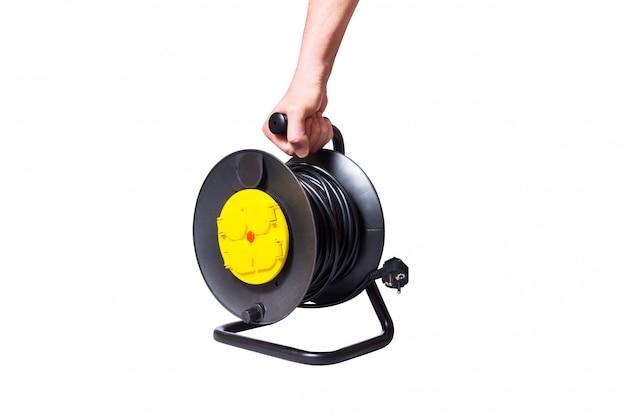 Mann habd hält schwarzes elektrisches verlängerungskabel auf einer aufwickelspule mit vier steckdosen