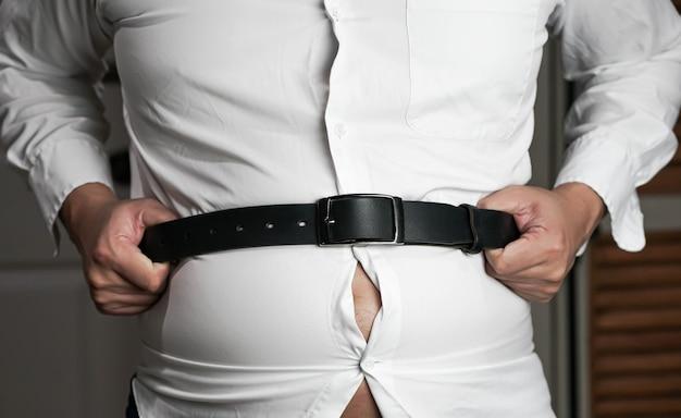 Mann hält an seinem gürtel und bauch, übergewichtig.