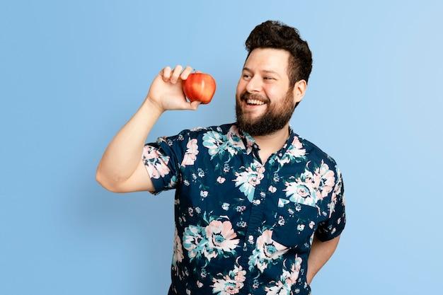 Mann hält apfel für eine kampagne für gesunde ernährung