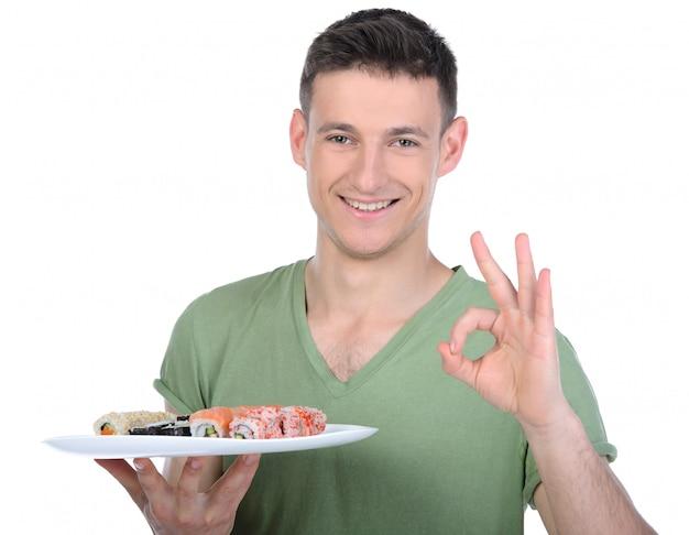 Mann hält auf sushi-teller und zeigt geste ok.