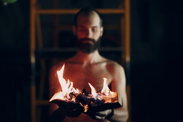 Mann hält brennendes buch in seinen händen.