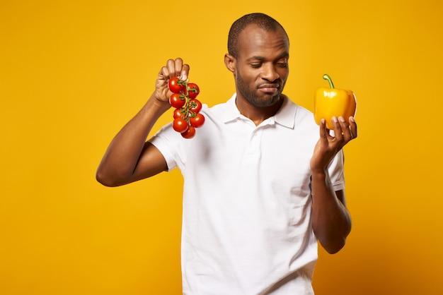 Mann hält bündel tomaten und gelben grünen pfeffer.
