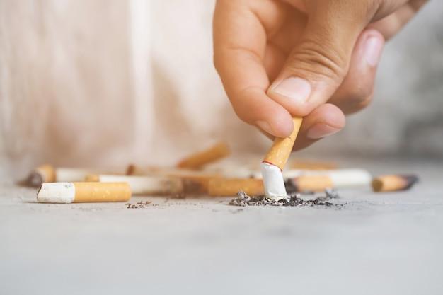 Mann hält das rauchen einer zigarette in der hand dunkel.