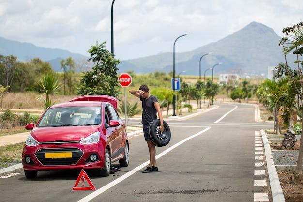 Mann hält den ersatzreifen gegen ein kaputtes auto vor dem hintergrund von bergen und palmen