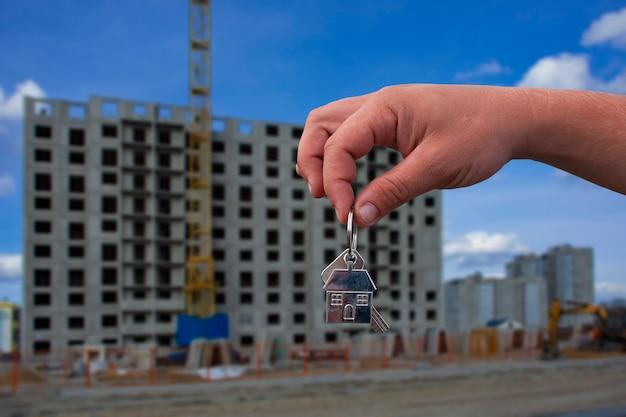 Mann hält die schlüssel zum haus in seinen händen vor dem hintergrund eines mehrstöckigen gebäudes. konzept für den kauf und die vermietung von wohnungen.