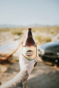 Mann hält ein kaltes bier be