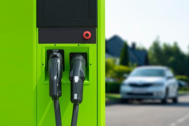 Mann hält ein smartphone mit einem digitalen kraftstoffzähler auf dem bildschirm im hintergrund einer tankstelle und eines autos.