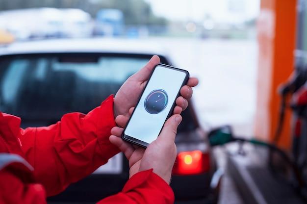 Mann hält ein smartphone mit einem digitalen kraftstoffzähler auf dem bildschirm im hintergrund