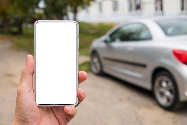 Mann hält ein smartphone mit leerem bildschirm in der linken hand in der nähe des geparkten fahrzeugs. person auf der straße verwendet die autolink-anwendung auf dem handy. fernstart des motors über die telefon-app. reisecomputer starten.