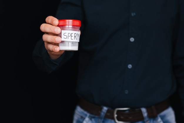 Mann hält eine bank der samenzellen in seiner hand