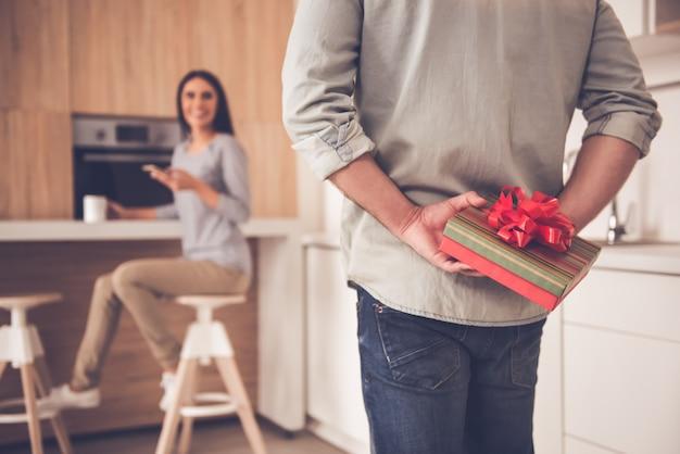 Mann hält eine geschenkbox hinter seinem rücken