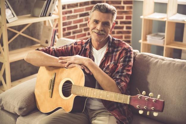 Mann hält eine gitarre, betrachtet kamera und lächelt.