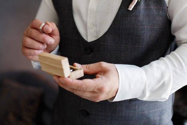 Mann hält eine holzkiste mit eheringen nahaufnahme bräutigam am hochzeitstag