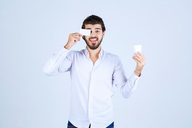 Mann hält eine kaffeetasse in der einen hand und präsentiert seine visitenkarte in der anderen hand