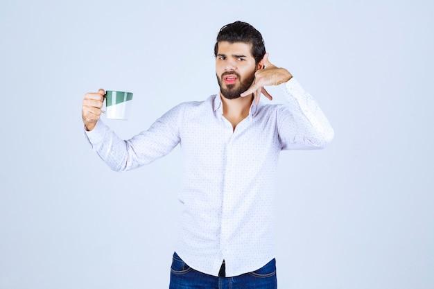 Mann hält eine kaffeetasse und bittet um einen anruf