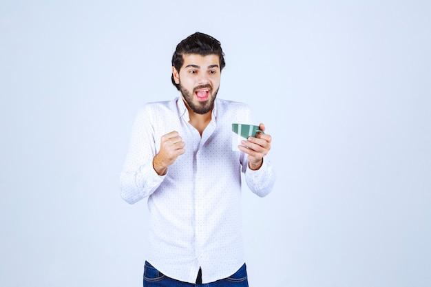 Mann hält eine kaffeetasse und fühlt sich mächtig