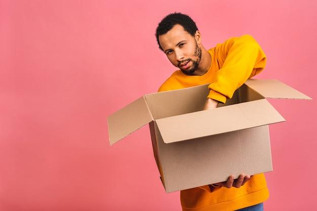 Mann hält eine leere box isoliert über rosa. lieferkonzept.