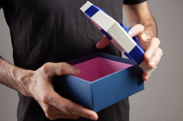 Mann hält eine offene geschenkbox