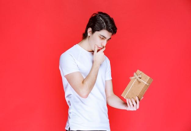 Mann hält eine pappgeschenkbox und sieht verwirrt aus.