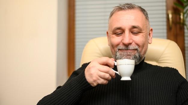 Mann hält eine tasse tee hoch