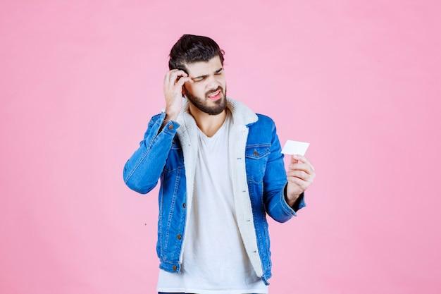 Mann hält eine visitenkarte und sieht verwirrt aus