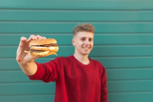 Mann hält einen appetitlichen burger in den händen und zeigt ihn auf türkis