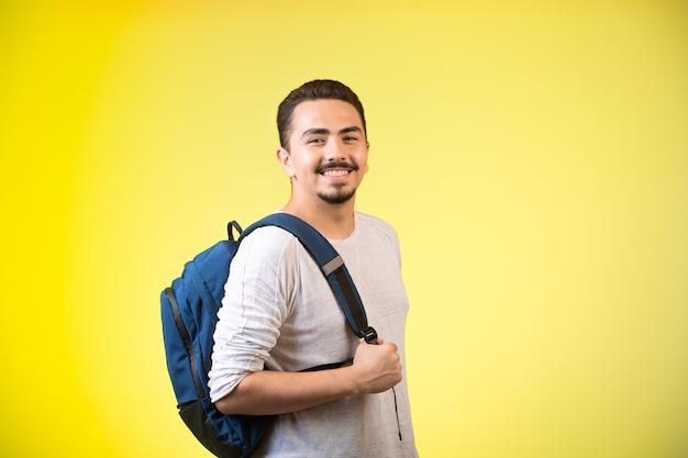 Mann hält einen blauen rucksack und sieht glücklich aus.