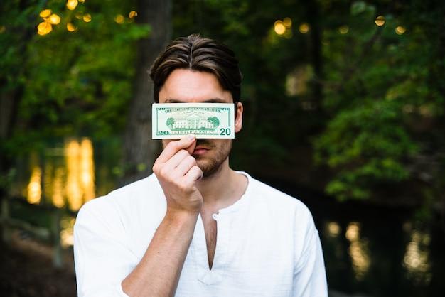 Mann hält einen dollarschein und versteckt sein gesicht, das seine persönlichkeit durch kapitalismus zensiert.