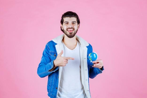 Mann hält einen globus und versucht einen ort zu finden