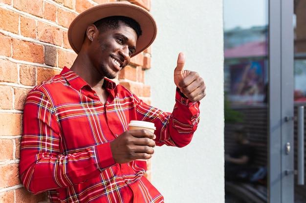 Mann hält einen kaffee und macht die daumen hoch geste