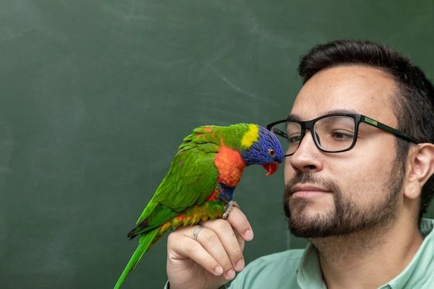 Mann hält einen papagei trichoglossus moluccanus