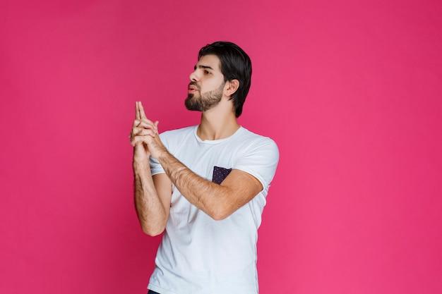 Mann hält finger wie eine waffe.