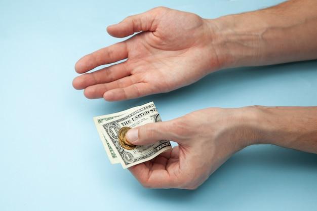 Mann hält geld in seinen händen und eine handfläche nach oben.