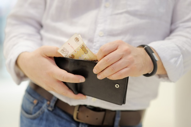Mann hält geldbörse mit russischem papiergeld (rubel)