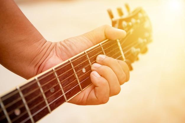 Mann hält gitarre mit sonnenlicht