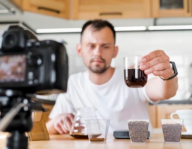 Mann hält glas kaffee