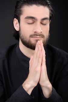Mann hält hände nahe kinn und betet.
