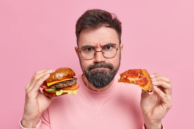 Mann hält hamburger und pizza presst lippen trägt einen runden brillenpullover