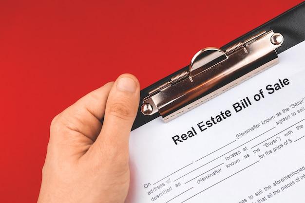 Mann hält immobilien-kaufformular. hypothekenkonzept. rotes hintergrundfoto