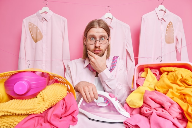 Mann hält kinn hat überraschten ausdruck, der damit beschäftigt ist, wäsche zu bügeln, wäscht zu hause trägt runde brille trägt hemdposen drinnen auf rosa