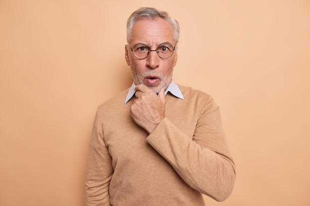 Mann hält kinn reagiert emotional auf nachrichten schaut schockiert in die kamera trägt optische runde brille lässiger pullover isoliert auf braun